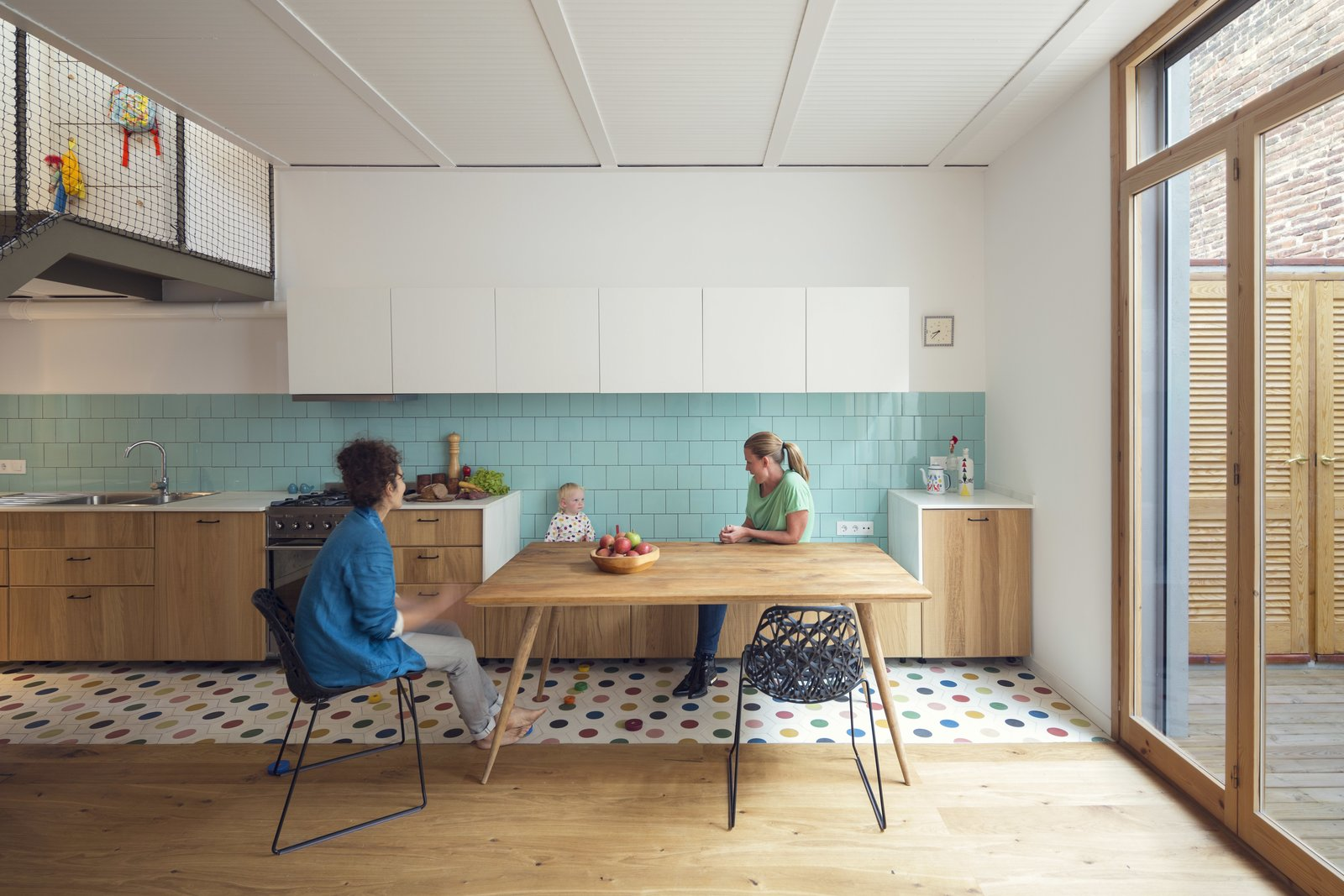 A narrow band of ceramic tiling delineates the compact kitchen from the rest of the room. Built-in cabinetry doubles as seating to help integrate the kitchen into the dining area. The table from Maison du Monde spans the subtle divide.  A 16-Foot-Wide Barcelona Row House Gets Creative to Stay Bright and Airy by Alex Vuocolo