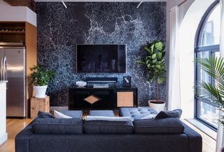 In the open-plan living area, a wall covered in Calico's Lunaris Midnight—inspired by moonscapes and outer space—sets the tone for a vignette of darker furnishings, including a vintage credenza that doubles as an entertainment center, equipped with a Sonos Playbar.