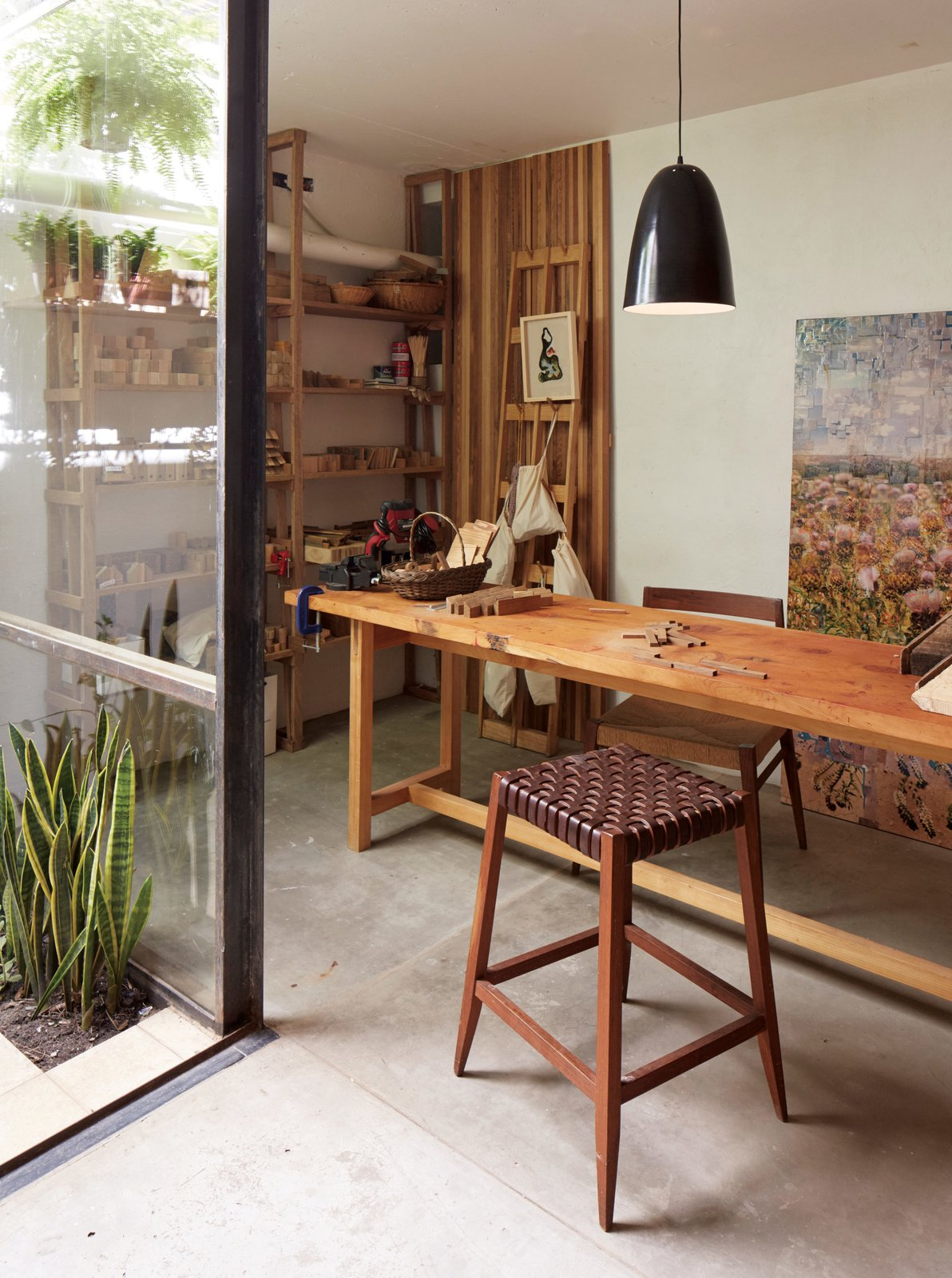 Office, Craft Room Room Type, Desk, and Concrete Floor In her workshop, which features a Mercedes table, an Otto lamp, and a wood-and-leather bar stool, all by NET, she creates a line of uncomplicated wood toys called Sarmiento.  Photo 9 of 10 in One-of-a-Kind Furniture Fills This Delightfully Serene Buenos Aires Home