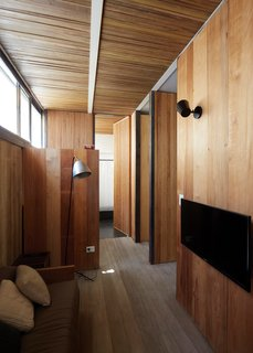 Wood envelops the home's second story. The floor is made of Brazilian pine salvaged from a warehouse. The walls are also recycled boards, sourced from the ceiling of a conventillo, or tenement, in the La Boca neighborhood, and sliced into 12-inch-wide planks. The ceiling is made of ipe from the NET workshop. In the family room, cushions knit by Teresa's mother, Griselda Sposari, sit on a Lennon armchair by NET.