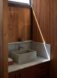 A Carrara marble sink in the bathroom is surrounded by Brazilian pine and cypress.