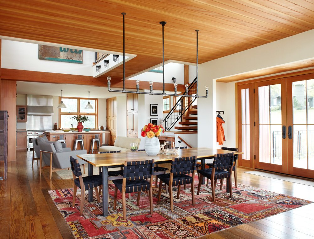 The aluminum pipe light fixture and white oak dining room table—made from the original barn's horse stalls—were both DIY projects completed by one of the homeowners and their friend, respectively. A design from The Rug Company, made from patches of old rugs, sits under the table.  A Family Salvages an 1880s Barn to Create Their Nearly-Net Zero Escape by Caroline Wallis