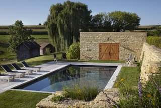 The old barn's foundation, re-stacked by a local stonemason, was reused as a rustic retaining wall for the pool area. The property also came with a corn crib and blacksmith shop as old as the barn, seen behind the pool, which are both used for storage now. St. Tropez chaises from Kingsley-Bate line the pool.