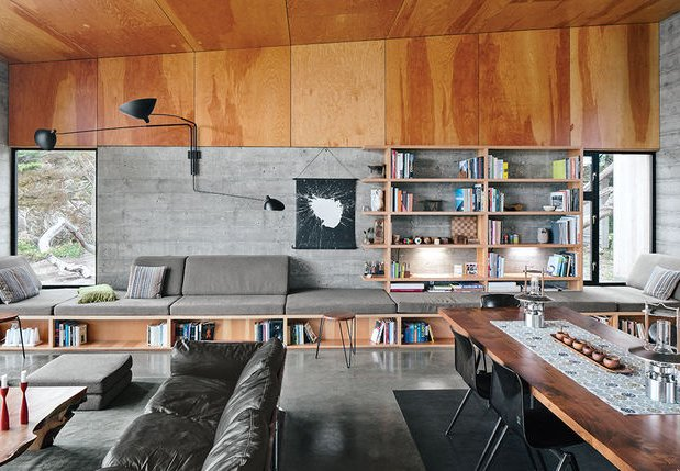 The exposed concrete in the living room of a Sea Ranch, California home brings out the warmth of the plywood ceilings and Douglas fir built-ins.  Striking Exposed Concrete Interiors by William Harrison