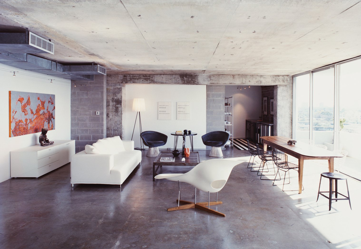 """When Barbara Hill purchased a 1960s Houston condo she completely stripped its interior, seeking a minimal restart. When the apartment was down to its original mottled concrete walls and floors Hill decided to keep everything exactly the way it was. """"Once I saw the exposed space, I couldn't bear to put anything back,"""" she says.  Striking Exposed Concrete Interiors by William Harrison"""
