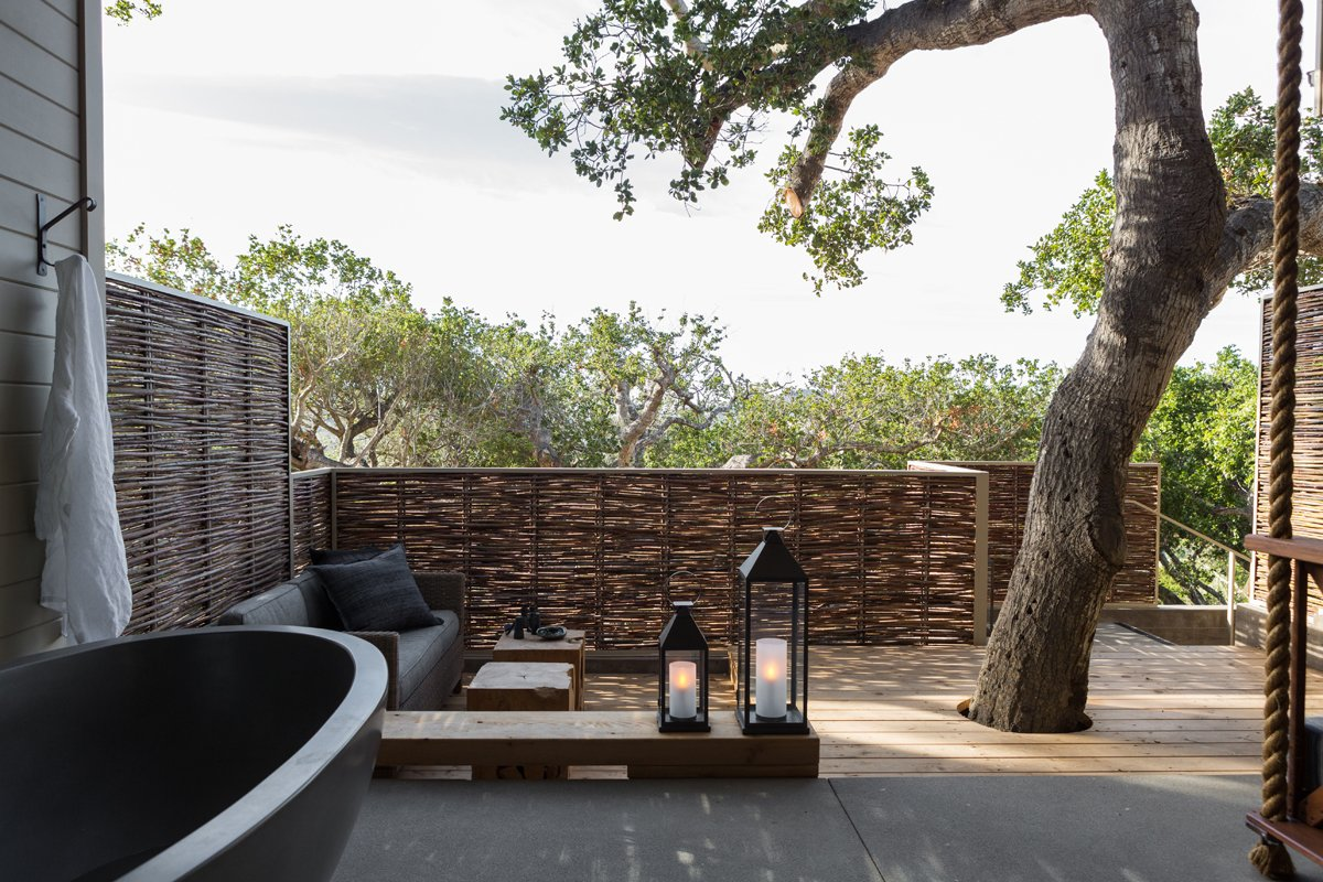 """""""My philosophy is to keep it simple,"""" Hollis says. """"I prefer to work with natural materials such as wood, steel, concrete, rope, and burlap, and to see how they interact with each other."""" A live oak tree shades the deck. The lanterns are from Restoration Hardware, with custom wiring and modifications from Hollis's team.  A Serene Hotel in Carmel, California by Diana Budds"""