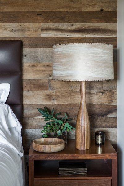 "A vintage wood lamp and turned bowl stands next to the bed. ""We wanted to incorporate elements used in residential homes,"" Hollis says of the eclectic medley of accessories and furnishings in the space. ""These would be items that you would collect over time. They don't exactly match, but they all work together—they create a relaxed casual environment while still elevating the interior and amenities to what you expect from a world-class luxury property."""