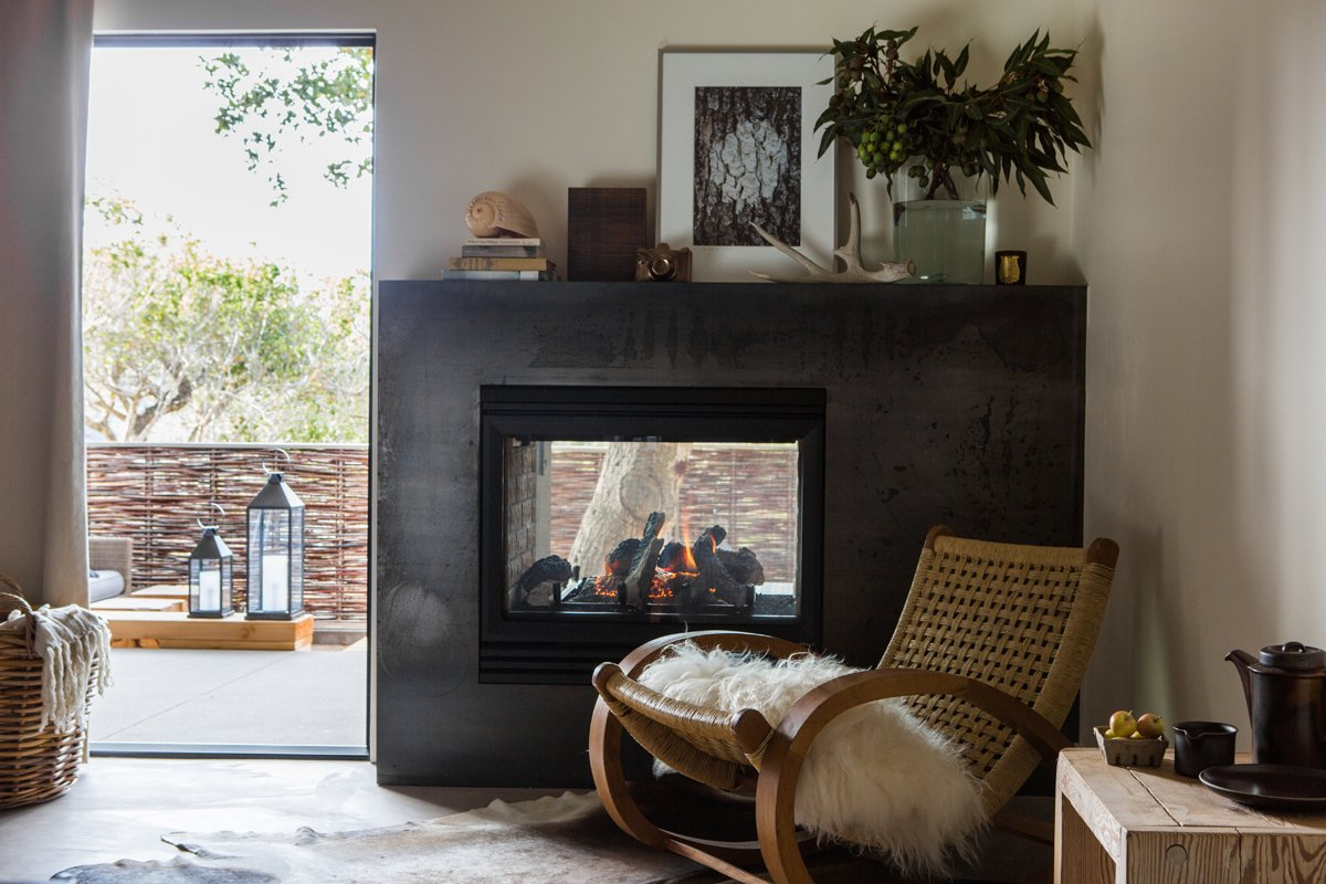 The double-sided fireplace is wrapped in a custom surround made fron Cor-Ten steel. The rocker is vintage and the artwork is from the Lost Art Salon.  A Serene Hotel in Carmel, California by Diana Budds