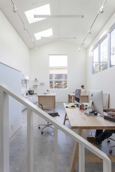 """The double-height artist studio showcases custom pieces by Dovetail, like a metal handrail and maple work tables, as well as Eames Aluminum Group chairs. The goal for the home, says Heliotrope principal Mike Mora, was to, """"Create an interior space akin to an art gallery with white wall surfaces adequate to hang art."""""""