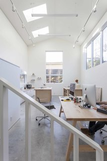"The double-height artist studio showcases custom pieces by Dovetail, like a metal handrail and maple work tables, as well as Eames Aluminum Group chairs. The goal for the home, says Heliotrope principal Mike Mora, was to, ""Create an interior space akin to an art gallery with white wall surfaces adequate to hang art."""