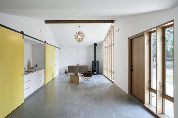 To evoke the structure's past as a horse stable, and provide options for the use of the space, Schaer and his team employed Sing Core sliding barn doors mounted on Krownlab's Axel hardware. The sliding track runs the full width of the building, allowing residents to open or conceal a bedroom, kitchenette, and entrance to an adjacent 530 square-foot garage, all depending on how the spaces are being used. The kitchenette, seen left, features a Kraus sink and a chrome Grohe Concetto faucet.