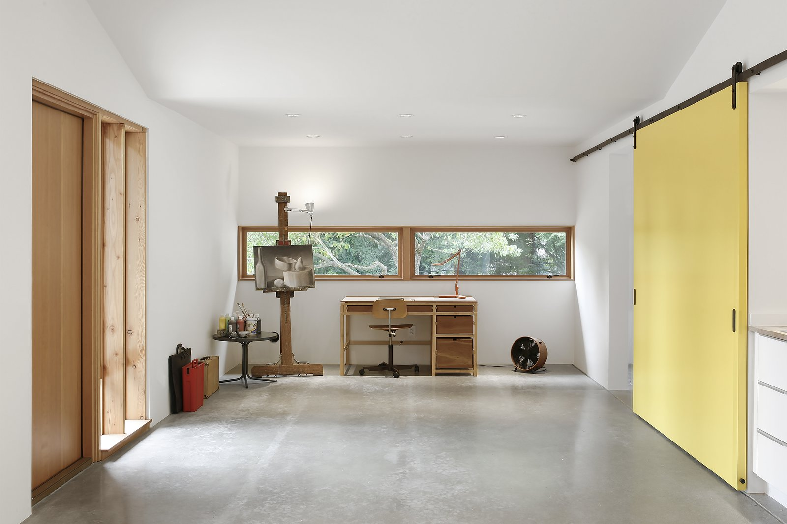 """Office, Craft Room Room Type, Desk, Chair, and Concrete Floor """"Concrete floors, drywall, and minimal use of trim allowed for the feel of the space to remain utilitarian, while exposed Douglas fir structural members created a connection to regional Pacific Northwest design,"""" Schaer says. The clients wanted a place for painting and occasional freelance work, which fits opposite the room's fireplace and seating area. A Kevi Chair by Jørgen Rasmussen accompanies the desk.  Horse Stable Studio by Kelly Dawson"""