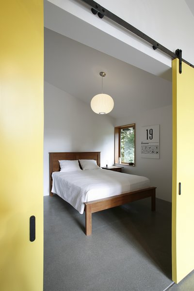 """""""Completing the sequence [of the structure] is the bedroom and bathroom, beyond the barn door threshold, designating them as the least frequently used spaces,"""" Schaer says. For now, grandparents can use the bedroom when they visit, but the owners also hope to rent it out one day. The George Nelson Bubble Lamp is from Modernica."""