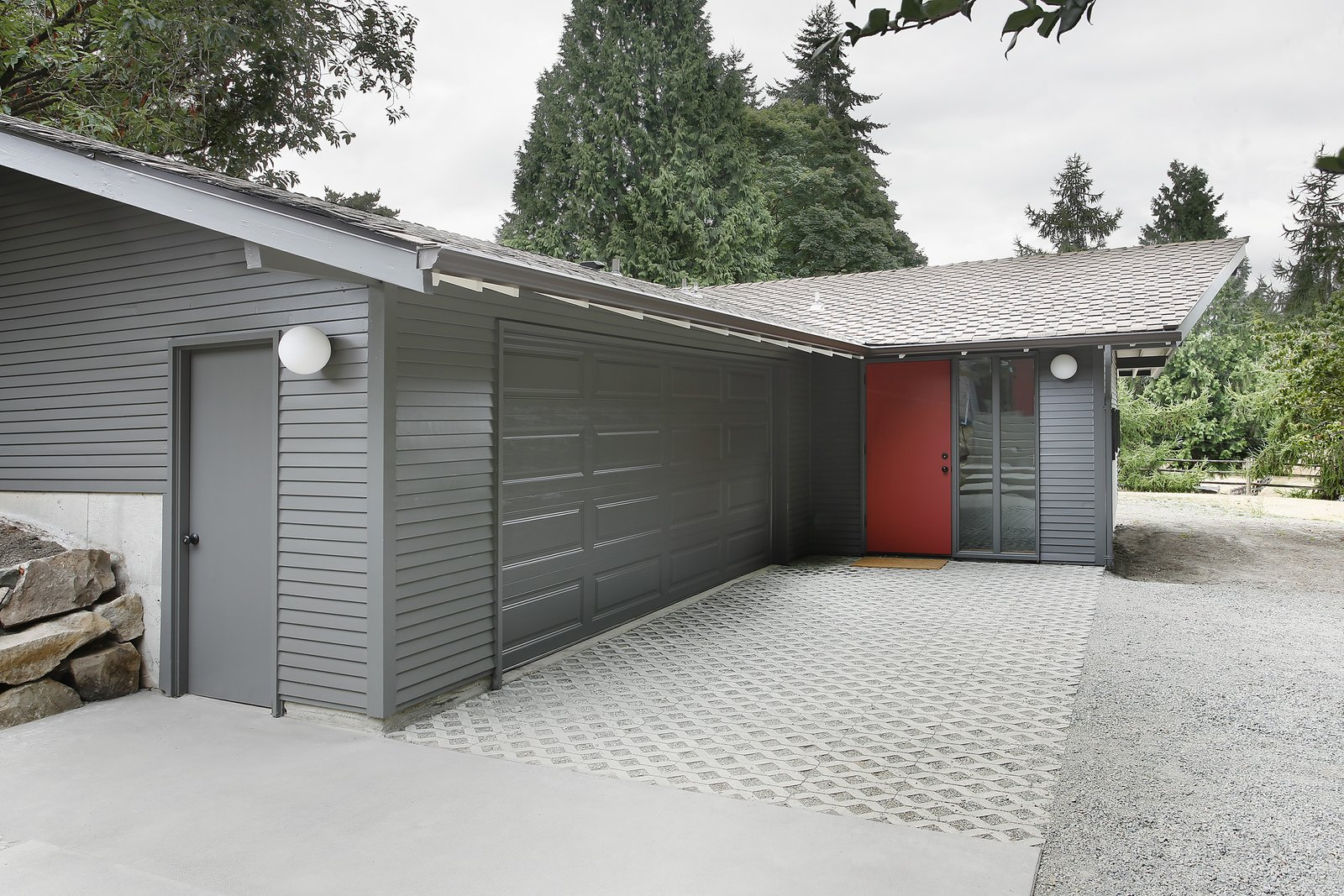 """Exterior, House Building Type, Shingles Roof Material, Wood Siding Material, and Gable RoofLine """"The stable/garage was built with two intersecting gable roof forms,"""" Schaer says, which didn't match up with the inteiror spaces within. """"In order to provide a unified, singular main space, we dropped a flat ceiling at the entrance and linked it up with the main gable visible from the street.""""  Horse Stable Studio by Kelly Dawson"""