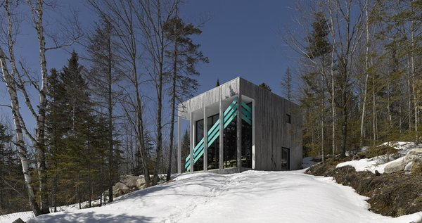 The home's exterior staircase features a diagonal handrail, constructed in three parts and painted slightly different turquoise tones. It contrasts with the surrounding landscape, adding dynamism and excitement to the otherwise simple, static structure of the home, which is clad in naturally weathered cedar siding.