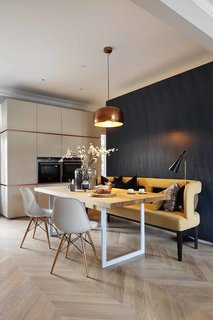 """The open dining room exemplifies a clients' wish for a """"fun yet minimalist"""" home. A copper Habitat pendant lamp hangs above a solid oak dining table fabricated by INTERIOR-iD. A whimsical mustard sofa pops against the blue Tabu veneer wall. Rather than competing, each piece brings a sense of tactility and warmth to the table, ultimately creating a unified look."""