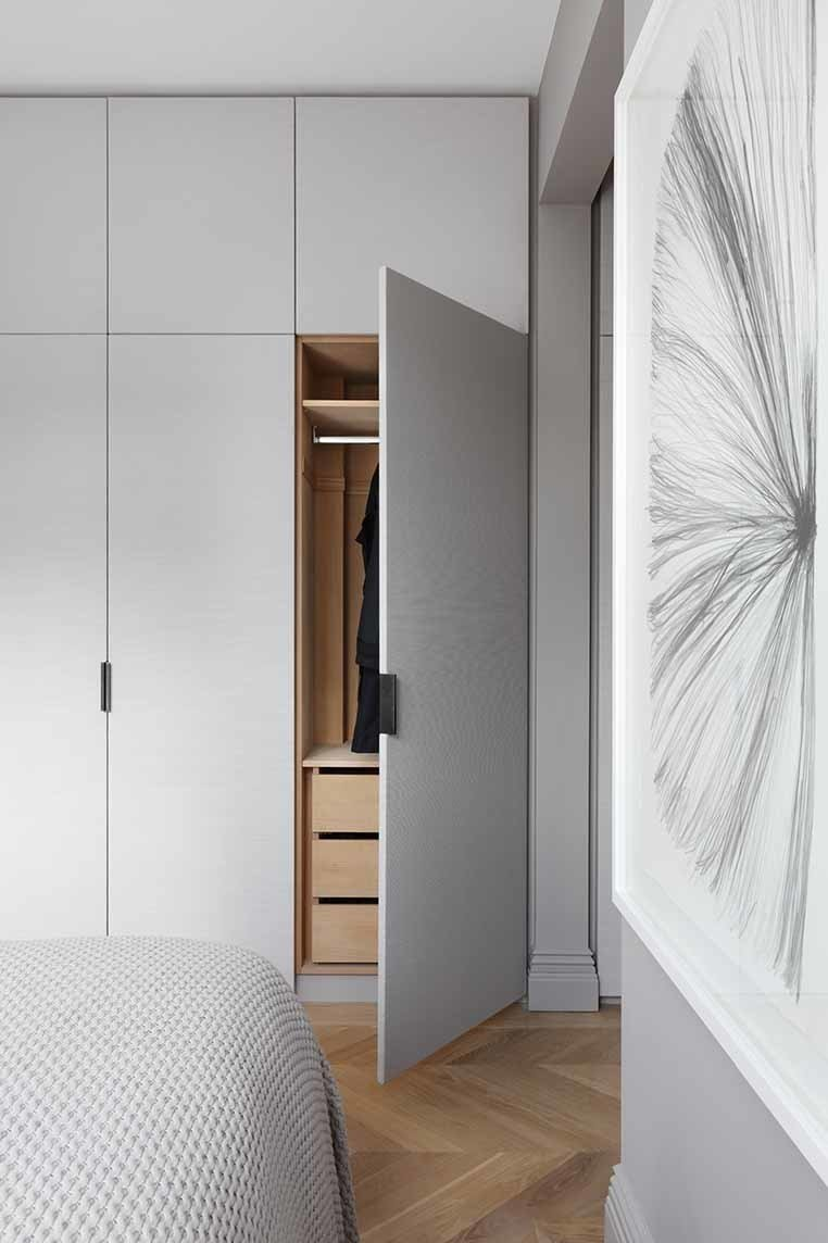 Fabric-clad wardrobe doors custom designed by INTERIOR-iD, along with Joseph Giles leather pulls, add texture to the master bedroom.  Two from Brass Is Everywhere at this Classical-Meets-Modern Flat in London