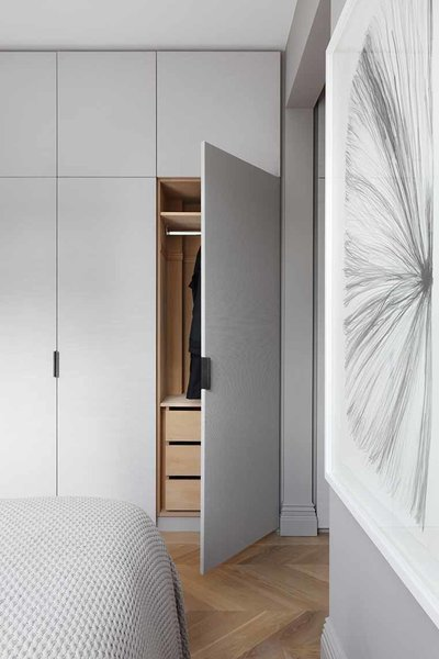 Fabric-clad wardrobe doors custom designed by INTERIOR-iD, along with Joseph Giles leather pulls, add texture to the master bedroom.  Storage by Dwell