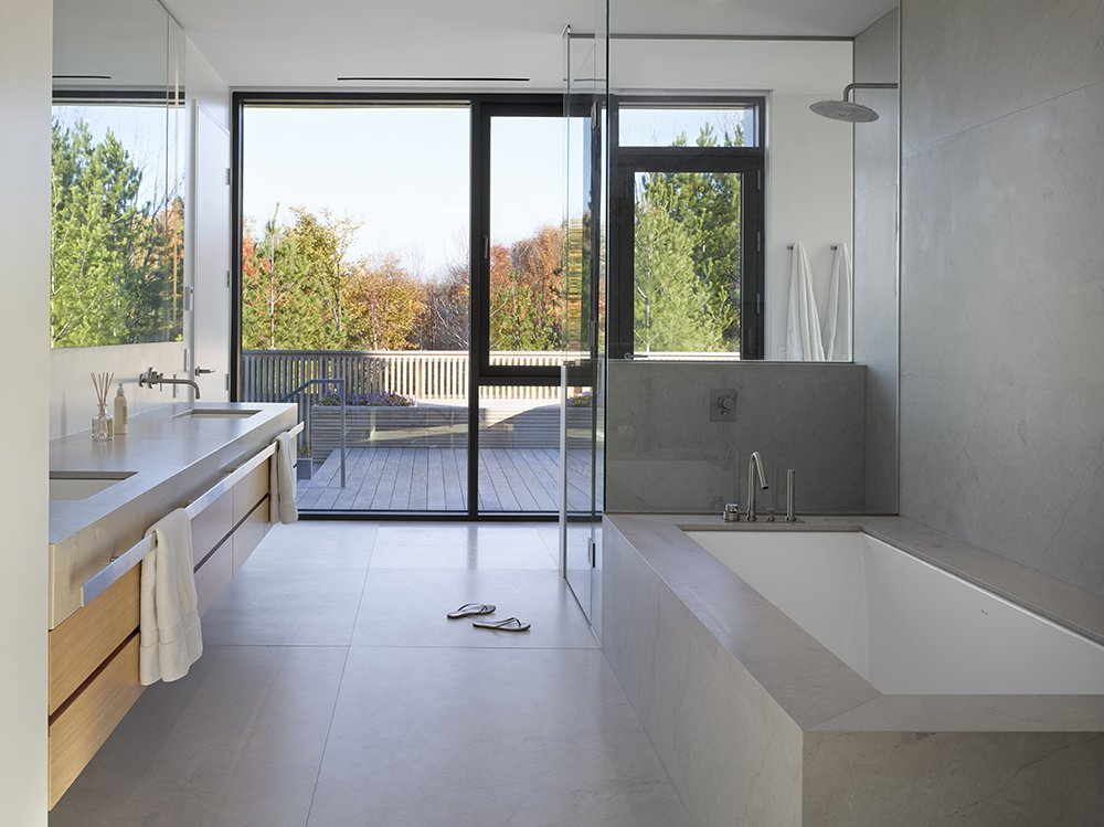 "Thanks to the clever placement of a cedar hot tub on the bathroom deck, rinsing off after a dip doesn't involve dripping water all over the house. The all-marble bathroom features Boffi Minimal Series fixtures.  Search ""five open decks"" from A Family Builds Their Dream Modern Home Overlooking the Georgian Bay"