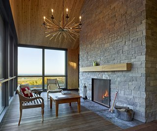 "A nod to the family's time in Switzerland, this chalet-like screened porch blends modern Swiss design sensibilities and the traditional architectural style of the Georgian Bay region. AKB explains,""The gabled form was inspired by the Long House, one of the earliest forms of permanent wood structures used in Ontario, which was used by both the First Nations and European settlers to shelter themselves in the harsh winter weather."" A Design Within Reach lounge chair complements the family's recycled furniture pieces from their original home."