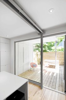 An aluminum-framed door leading to the terrace provides an added sense of depth, integrating outside with inside. Here, the metal contrasts sharply with the natural birch flooring.