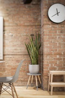 A succulent sits atop a stool from Zone Maison, juxtaposed against a warm brick wall.