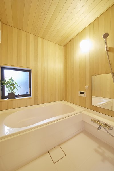 The bathroom's sauna-like interior includes a deep Toto bathtub—characteristic of traditional Japanese baths. The wooden hiba paneling, chosen because it is more water resistant than hinoki, is specific to the Northern Aomori region of Japan.