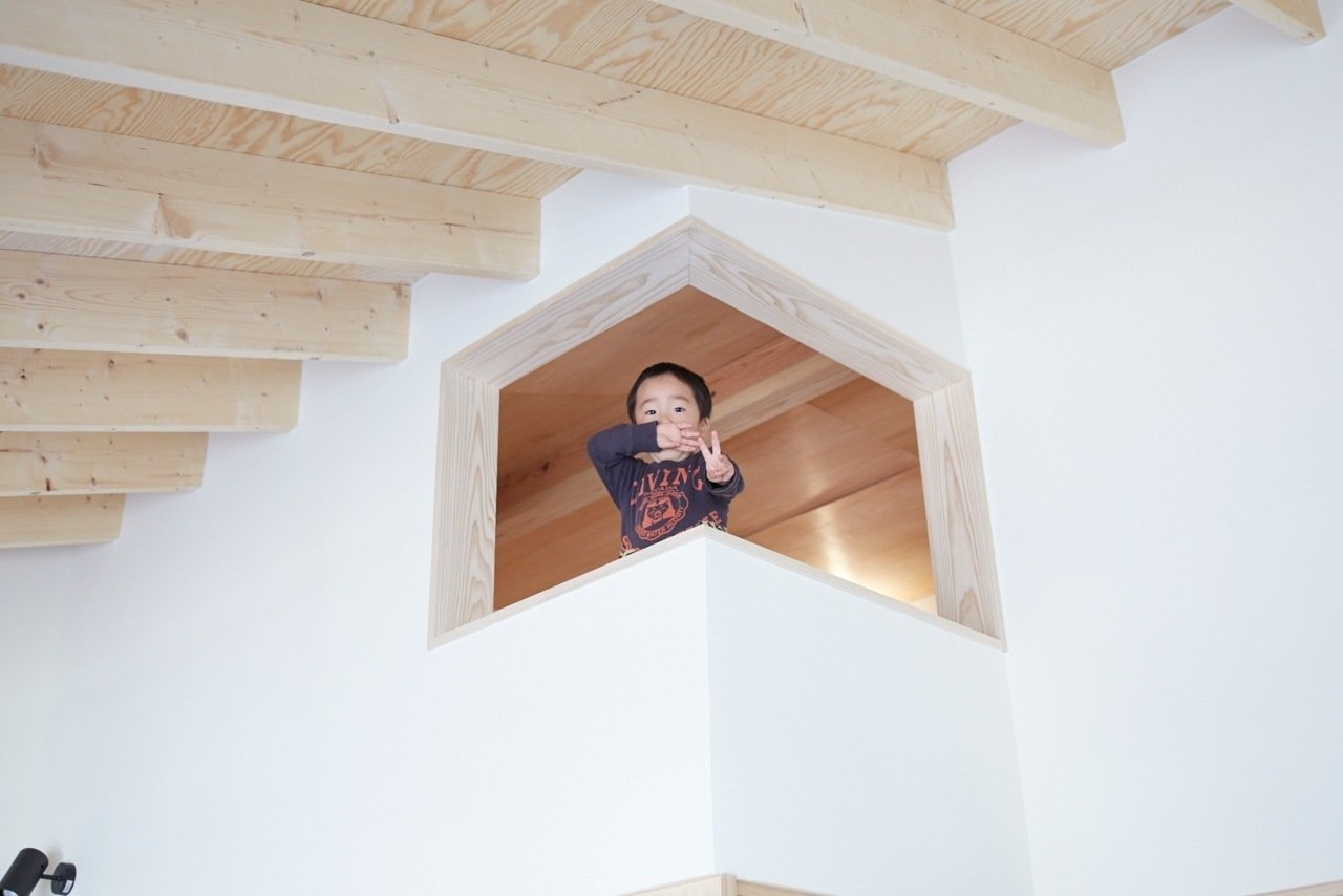 Kids Room and Playroom Room Type Takuma strikes a pose from the loft lookout as seen from the second floor. The loft is used for storage as well as a place for some peace and quiet.  Yanagisaki House by Caroline Wallis