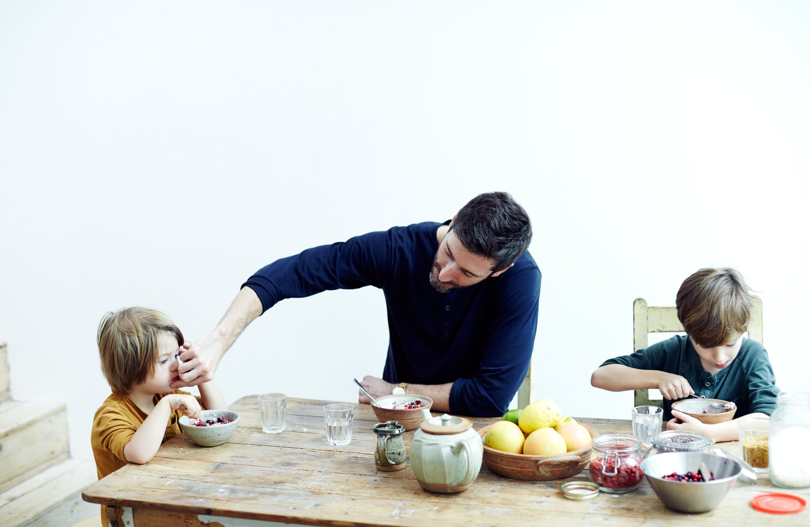 Dining Room, Chair, and Table In the Norton family home in London's Stoke Newington district, Jamie Norton and his sons, Miller, 3, and Ned, 7, enjoy a meal at a salvaged table and chairs found at a local vintage shop. The ceramics are by Richard Batterham.  Photo 1 of 9 in This Kitchen Is as Cozy as Your Favorite Coffee Shop—and That's Exactly the Idea