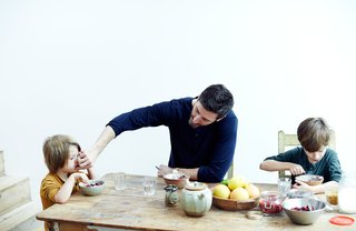 In the Norton family home in London's Stoke Newington district, Jamie Norton and his sons, Miller, 3, and Ned, 7, enjoy a meal at a salvaged table and chairs found at a local vintage shop. The ceramics are by Richard Batterham.