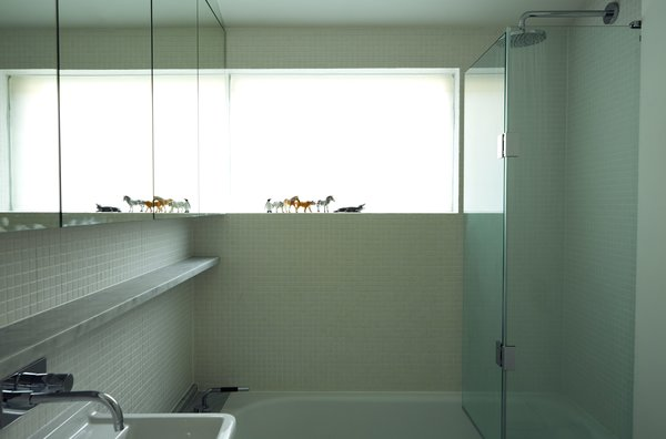 Sandblasted glass gives the bathroom window a frosted finish and—together with white mosaic tiles and mirrors—brightens the small space.