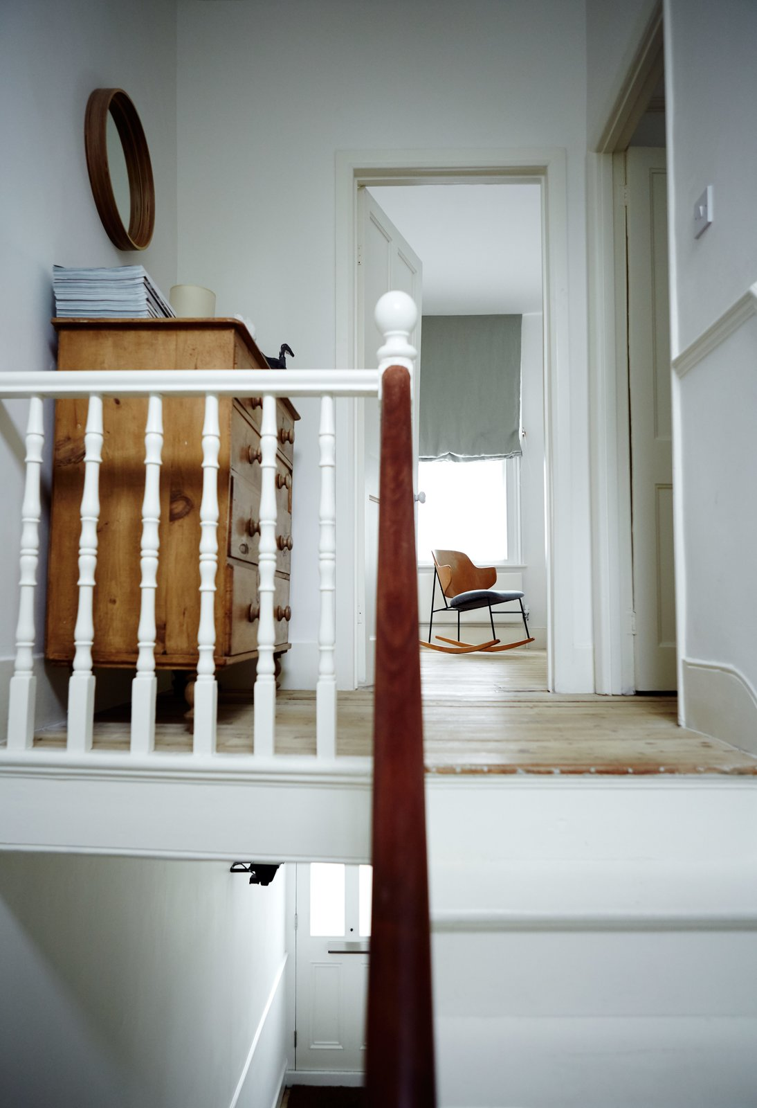 Staircase, Wood Railing, and Wood Tread At the top of the stairs, an Ib Kofod-Larsen rocker sits in the master bedroom  Photo 7 of 9 in This Kitchen Is as Cozy as Your Favorite Coffee Shop and That's Exactly the Idea