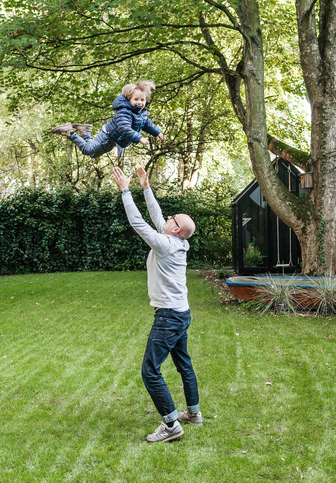 Fabian plays with Morten in the yard, which features a spacious lawn and a greenhouse. Tagged: Outdoor, Grass, and Back Yard.  Photo 7 of 12 in We Can't Get Enough of This German Apartment's Sleek Matte-Black Kitchen