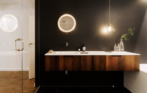 Here, a Universal vanity in acacia wood from Boffi was chosen to add some warmth, along with a stone floor with radiant heating. The mirror is a vintage design by Mathieu Matégot.