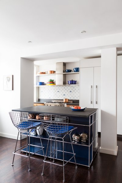 For a 1,500-square-foot condo in the Meatpacking District, Reddymade Design reconfigured the space to merge the kitchen, dining room, and living room into an open-plan arrangement. In the kitchen, the island unit is a modular piece by USM with a Vermont Black slate countertop. The Harry Bertoia stools are from Design Within Reach. The backsplash features Delft tiles, and the stove and range is Bertazzoni.