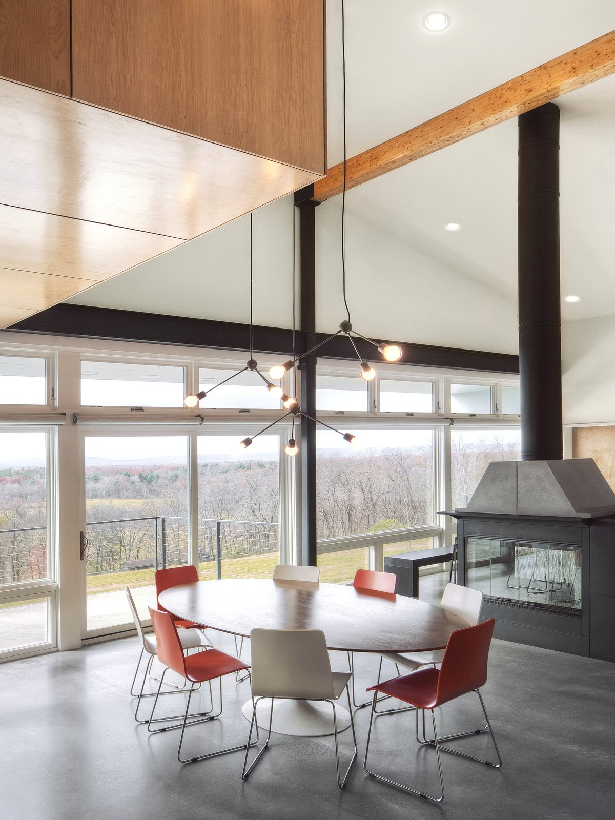 """""""The windows and patio doors, all made from super low-E insulated glass, open onto the amazing views and give easy access to expansive decks and a pool terrace,"""" Mulvena says. His team conducted solar studies and installed a retractable screen from MechoShade that would shade the house in the summer.  Hudson Valley Dream Retreat by Kelly Dawson"""