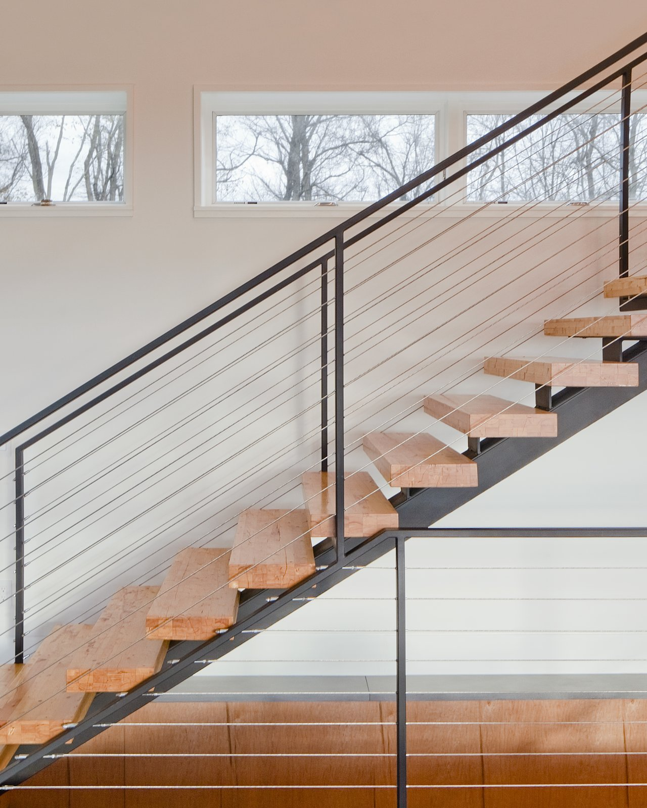 "Staircase, Metal Railing, and Wood Tread ""The clients desired a maintenance-free, year-round home using the ultimate in 'green' building methodologies,"" Mulvena says. The staircase is an example of the construction's mindset: it is made from the leftover laminated veneer lumber used on the roof.  Hudson Valley Dream Retreat by Kelly Dawson"