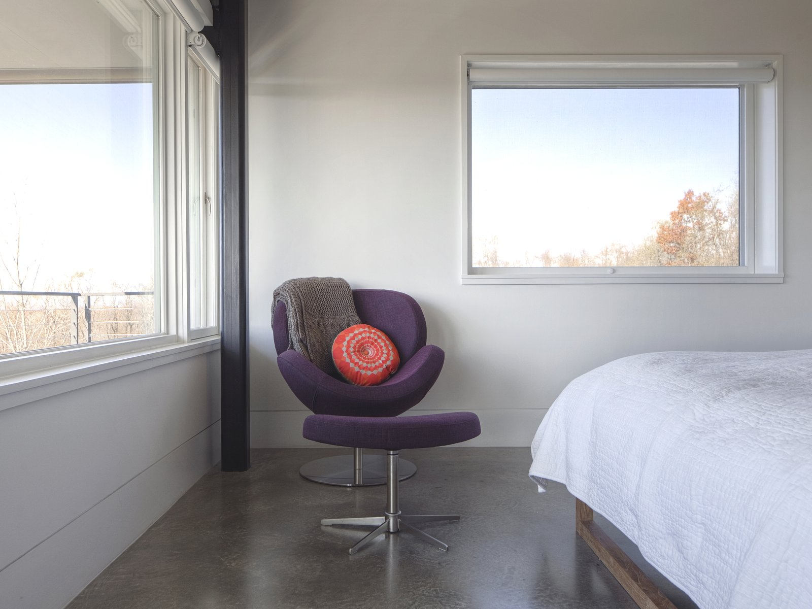 """""""The [owner] is a self-proclaimed minimalist who desired concrete throughout as a backdrop to her furniture, and eventually, her artwork,"""" Mulvena says. The Schelly chair and ottoman in the master bedroom are by BoConcept.  Hudson Valley Dream Retreat by Kelly Dawson"""