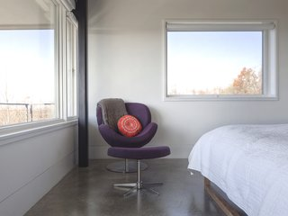 """""""The [owner] is a self-proclaimed minimalist who desired concrete throughout as a backdrop to her furniture, and eventually, her artwork,"""" Mulvena says. The Schelly chair and ottoman in the master bedroom are by BoConcept."""