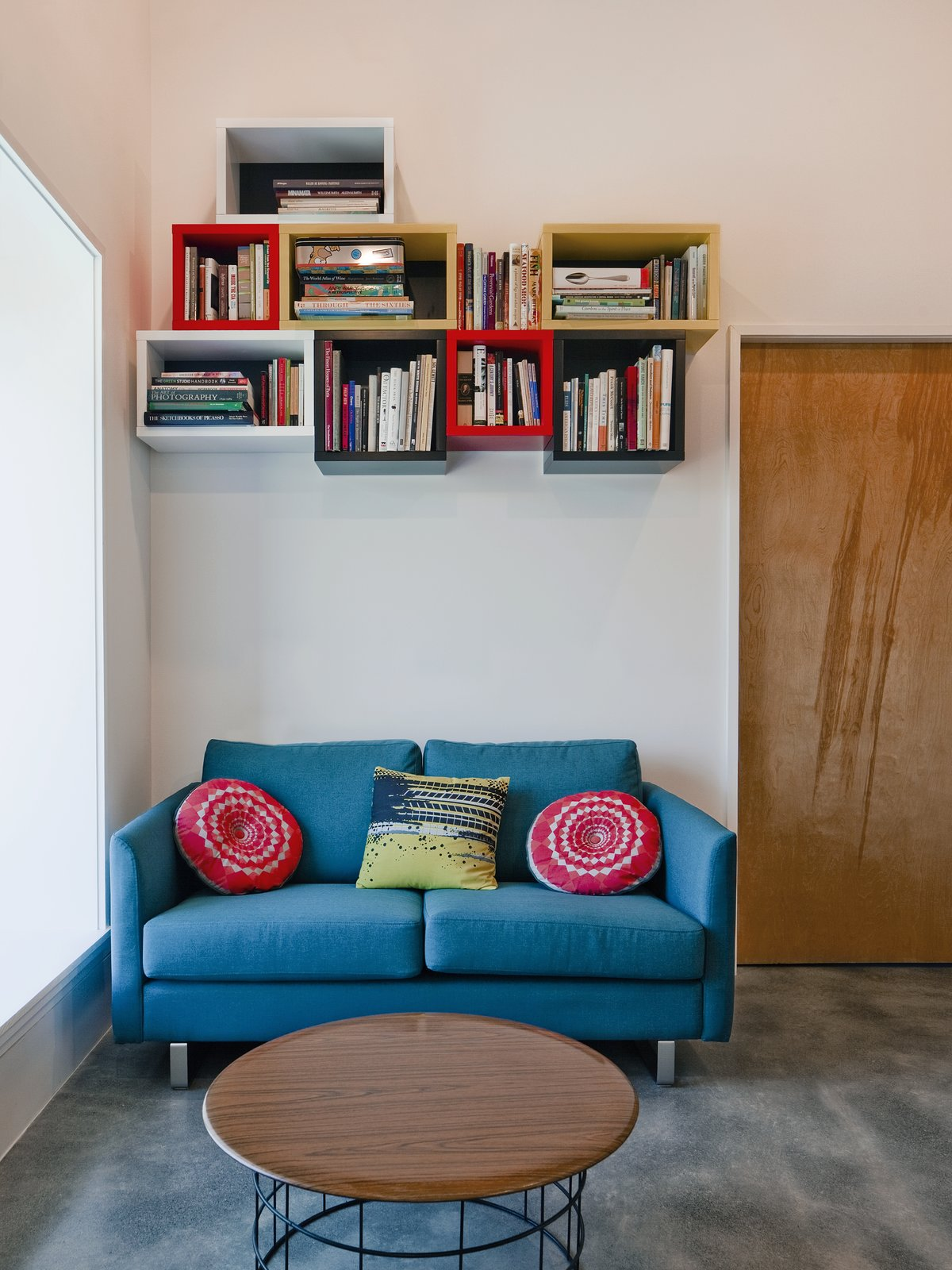 """Storage Room and Shelves Storage Type However, relying solely on concrete was not the best use of the budget, so Mulvena """"balanced the concrete floors and highlights with a simple palette of affordable but industrial materials: black steel and plywood."""" The couch is by BoConcept.  Hudson Valley Dream Retreat by Kelly Dawson"""