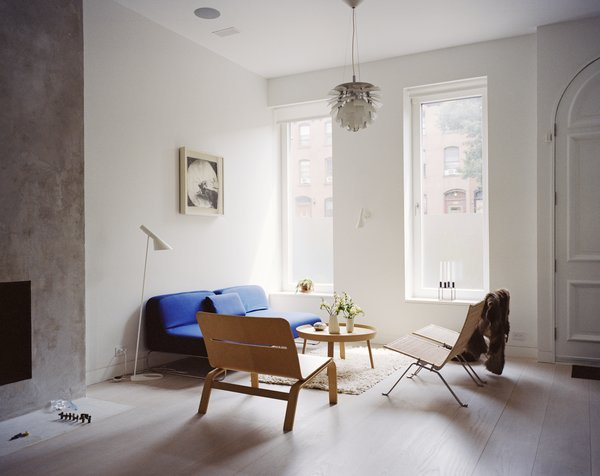 The living room is furnished with rattan chairs from Fritz Hansen, a Muuto side table, an Artichoke pendant by Poul Henningsen for Louis Poulsen, and a blue Living Divani sofa, one of a few color-popping accents found throughout.