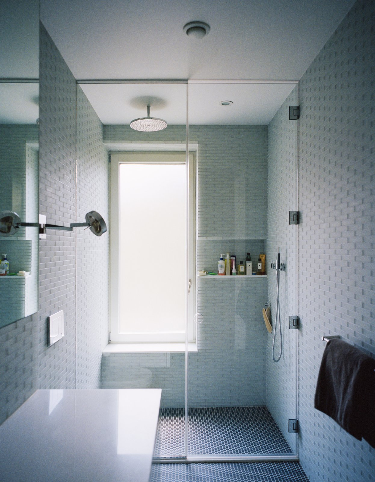 Bath Room, Open Shower, Recessed Lighting, and Ceiling Lighting Triple-glazed, frosted windows emit soft, filtered light against pale gray and blue surfaces inthe master bathroom. Lucian Field matte-glass and Lucian Mosaics penny round tiles, both by Ann Sacks, line the floor and walls.  Best Photos from Our Scandinavian Style Dreams Come True in This Brooklyn Town House