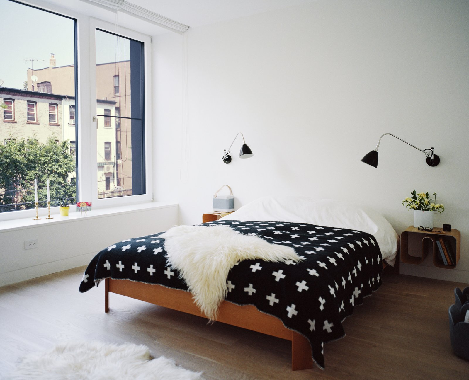 Bedroom, Bed, Light Hardwood Floor, Wall Lighting, and Night Stands Set atop a BoConcept bed, a graphic blanket by Pia Wallén for HAY punctuates the master bedroom. The sconces are by Robert Dudley Best for Bestlite.  Bedrooms by Dwell from Our Scandinavian Style Dreams Come True in This Brooklyn Town House