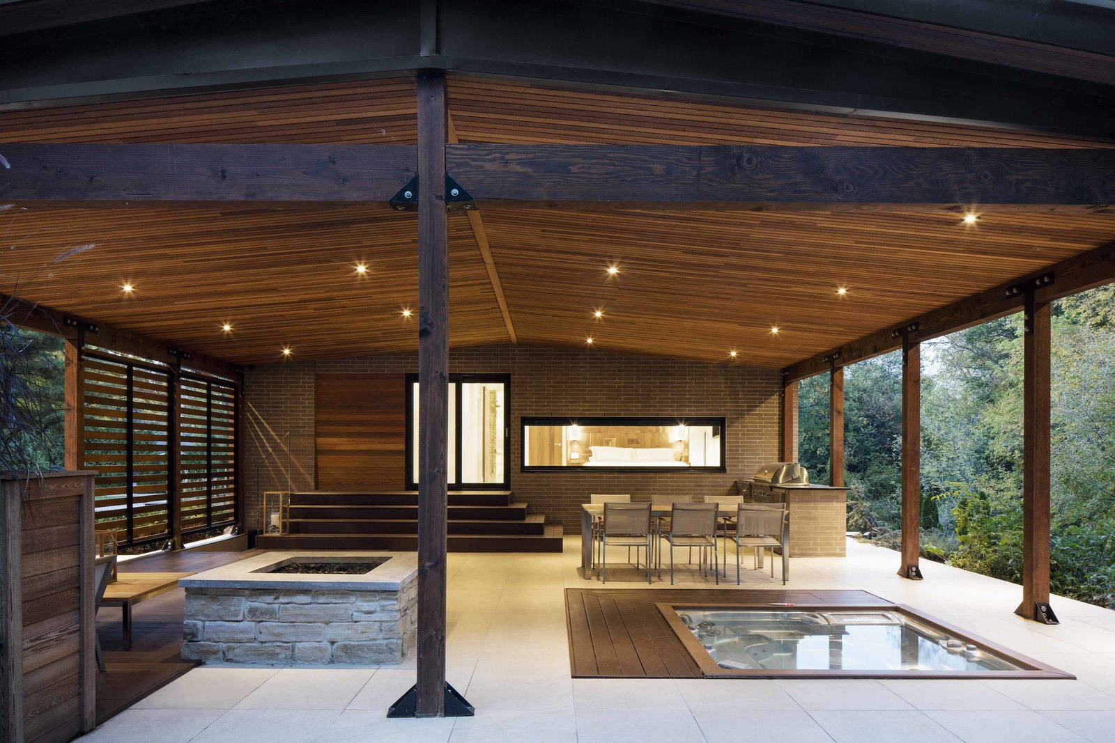 The open terrace is fitted with recessed lighting by Foscarini and a StoneTile floor. It houses an outdoor kitchen and dining area, as well as a fireplace and a spa. Inside, it connects to a gym and sauna in the basement.  Photo 4 of 12 in How to Refresh a Midcentury Gem in Quebec? Winter-White Everything