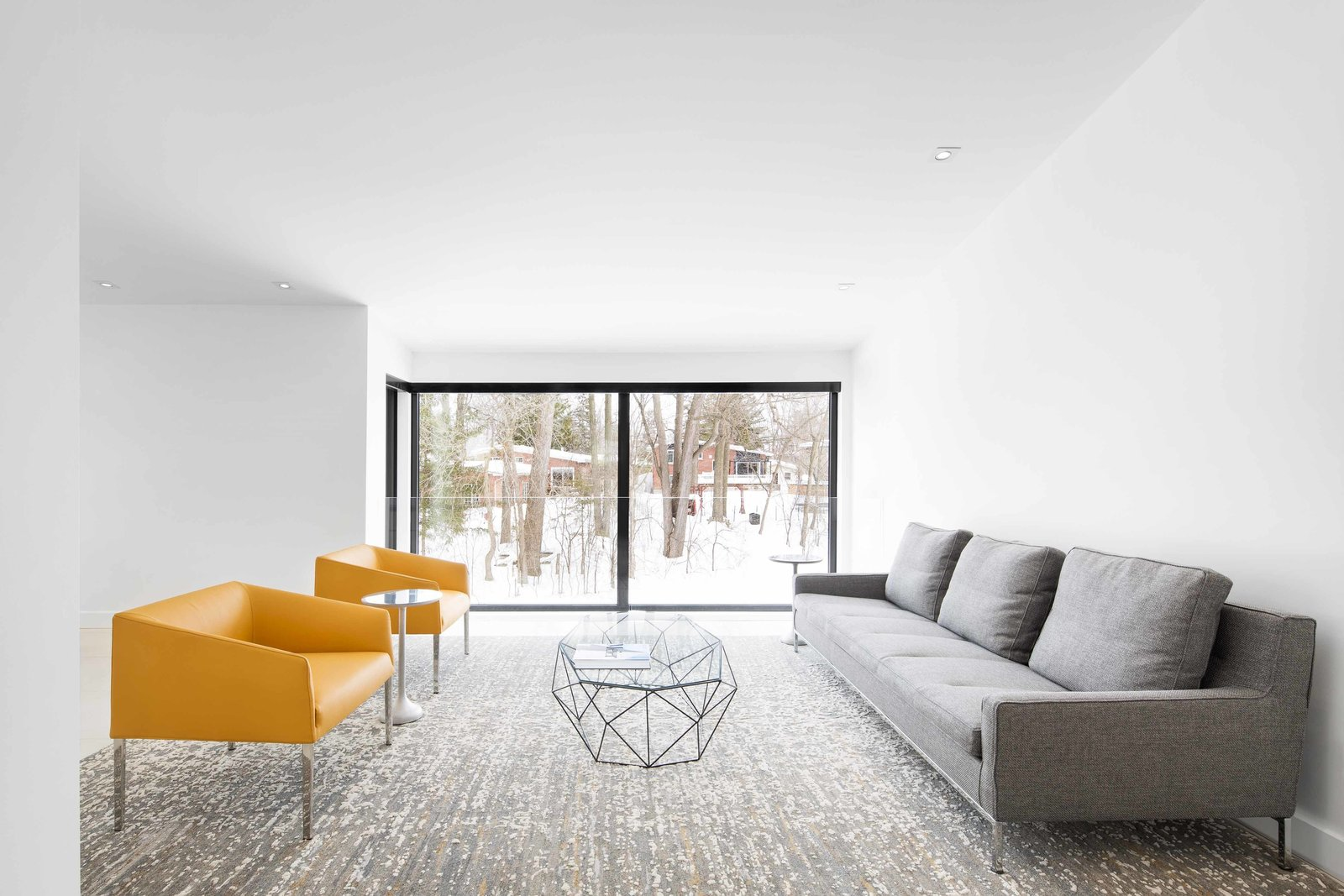 Living Room, Sofa, Chair, Coffee Tables, Rug Floor, and Recessed Lighting Horizontal lines and long, rectangular spaces train the eye towards the exterior. A glass and steel side table from Roche Bobois offers a geometric break from the linearity of the living room.  Photo 11 of 12 in How to Refresh a Midcentury Gem in Quebec? Winter-White Everything