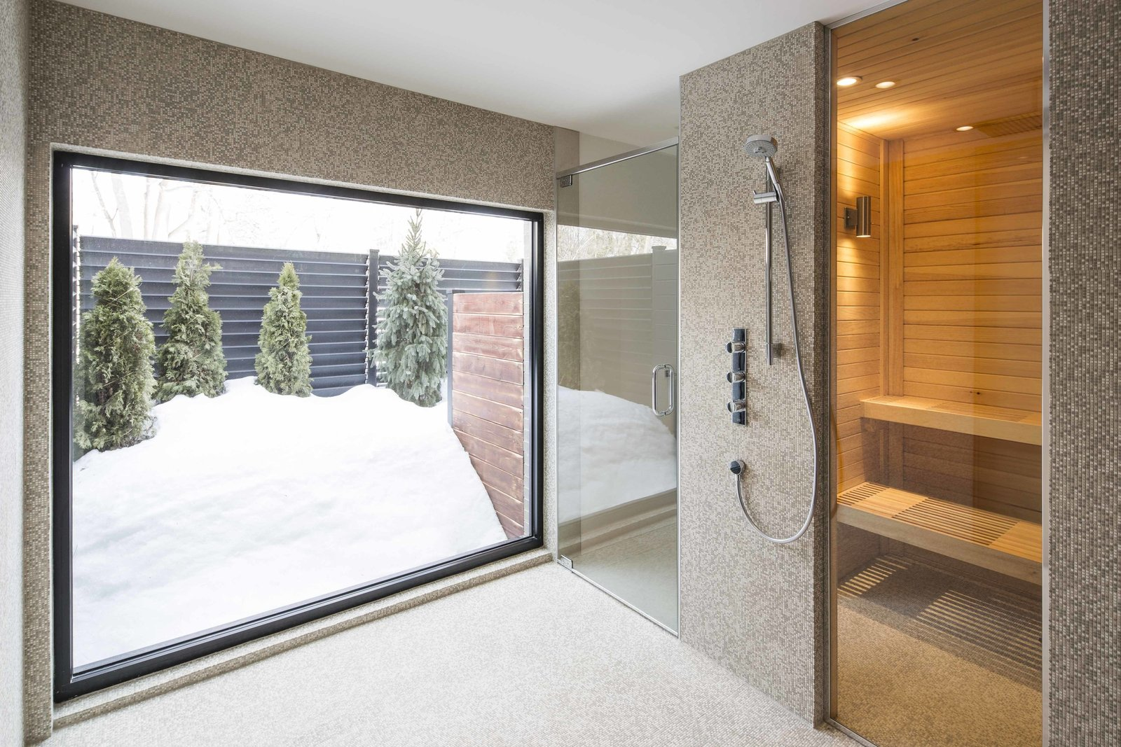 "Bath Room and Open Shower The lower floor houses a spa, gym, and office. A built-in bathroom by Espace Cuisine includes a sauna.  Search ""light filled metallic home embraces its wooded site"" from How to Refresh a Midcentury Gem in Quebec? Winter-White Everything"