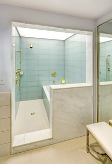 Large-scale glass tile lines the shower enclosure in the suite bathrooms; marble surrounds continue the material theme from the lobby.