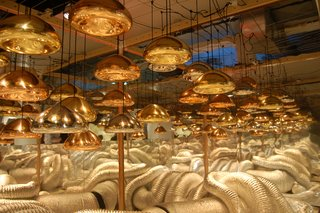 A collection of silver, brass, and copper Void Lamps by Tom Dixon.