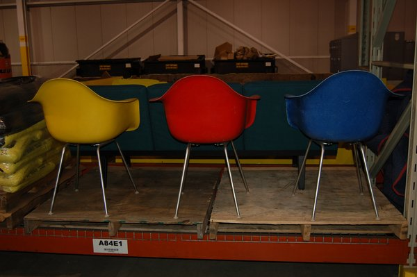 """We headed over to a big warehouse space to look for hidden gems. Here we see a trio of vintage Eames Plastic Arm Chairs, which were first produced in 1950. The Eames first introduced the chair in 1948 as their concept for the Museum of Modern Art's """"International Competition for Low-Cost Furniture"""". Originally conceived in stamped metal for the contest, the Eames and Herman Miller began exploring fiberglass as an ever lower-cost material option. The piece, which has gone through many iterations, was the first mass-produced plastic chair.  Inside the Herman Miller Headquarters by Amanda Dameron"""