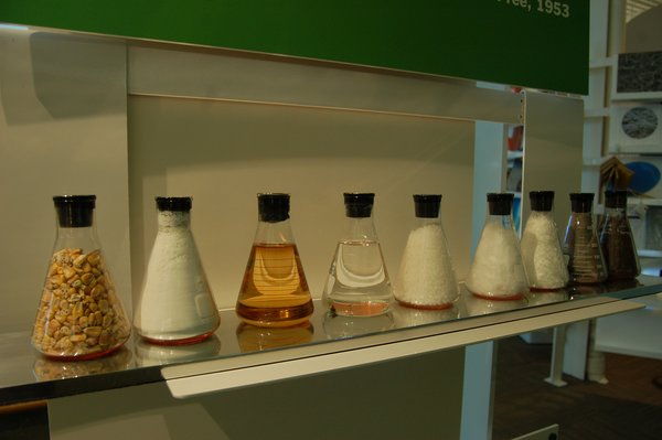 The first beaker shows corn kernels, then corn starch, then liquified, then purified, then synthesized into a corn-based polymer, then woven to a textile, and then the last beaker shows that when composted the fabric simply returns to the soil.  Inside the Herman Miller Headquarters by Amanda Dameron